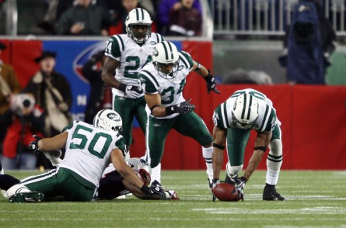 Jets Free Safety, Kerry Rhodes (25), recovers a fumble from Patriots' Tight End, Benjamin Watson. Watson's mistake ended a potential point-scoring drive.